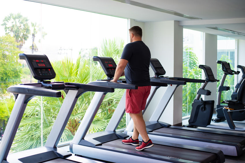 Full Male Runs On A Treadmill In A Gym. Concept Of Weight Loss And Sport. Back View.