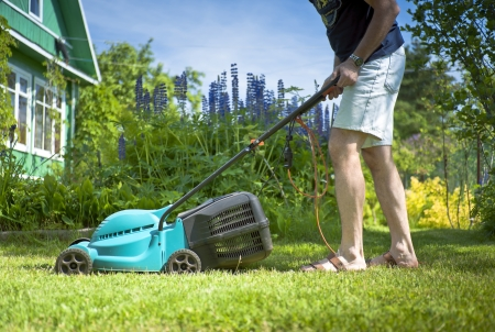 14238529 Man Mowing The Lawn In The Yard Of A Country House