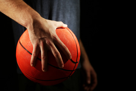 38075936 Basketball Player Holding Ball, On Dark Background