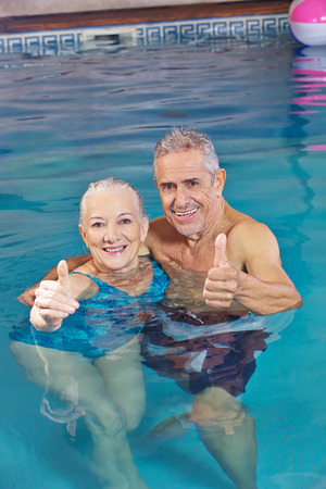 29990510 Happy Senior Couple Bathing In Swimming Pool Holding Their Thumbs Up