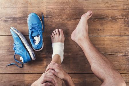39482245 Unrecognizable Injured Runner Sitting On A Wooden Floor Background