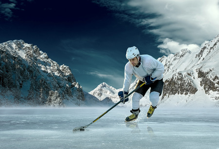51253981 Ice Hockey Player In Action Outdoor Around Mountains