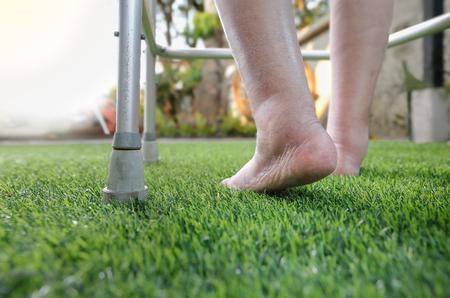 95082683 Elderly Woman Bare Swollen Feet On Grass With Walker